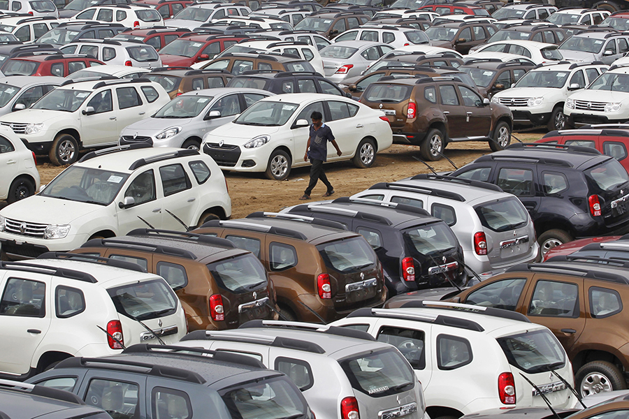 A worker walks past parked Renault cars at its stockyard on the outskirts of the western Indian city of Ahmedabad June 11, 2013. Car sales in India fell an annual 12.3 percent in May, an industry body said on Tuesday, dropping for the seventh straight month, as weak consumer sentiment in a slowing economy continued to weigh on demand. REUTERS/Amit Dave (INDIA - Tags: BUSINESS TRANSPORT EMPLOYMENT TPX IMAGES OF THE DAY) - GM1E96B1GAE01
